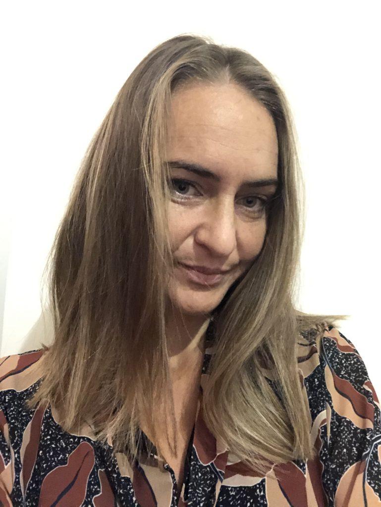 """dans """"A propos de moi"""" dans le Portfolio, portrait de Katarzyna Boduch - la tête tourné légèrement vers la gauche avec un léger sourire les cheveux demi-long detaché. On apperçoit la robe marron beige avec les motifs de feuilles. Tout sur un fond blanc"""